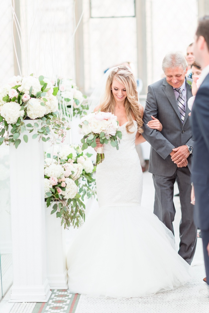 Bride walking down aisle with dad at museum wedding